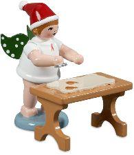 Weihnachtsengel am Tisch mit Mütze und Ausstechform